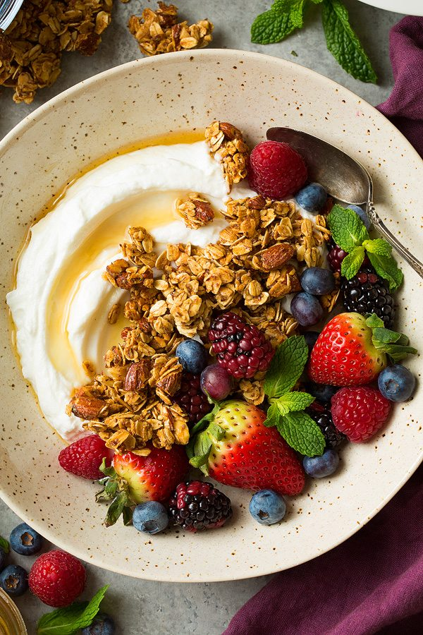 Close up image of granola, fresh berries, yogurt and honey in a speckled beige bowl.