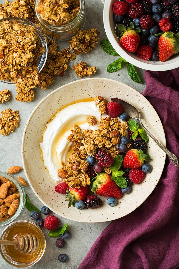 Granola in a bowl with Greek yogurt, fresh fruit and honey.