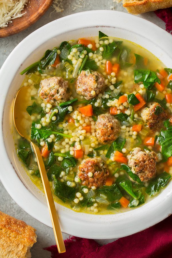 Closeup overhead image of Italian Wedding Soup in a large white bowl.