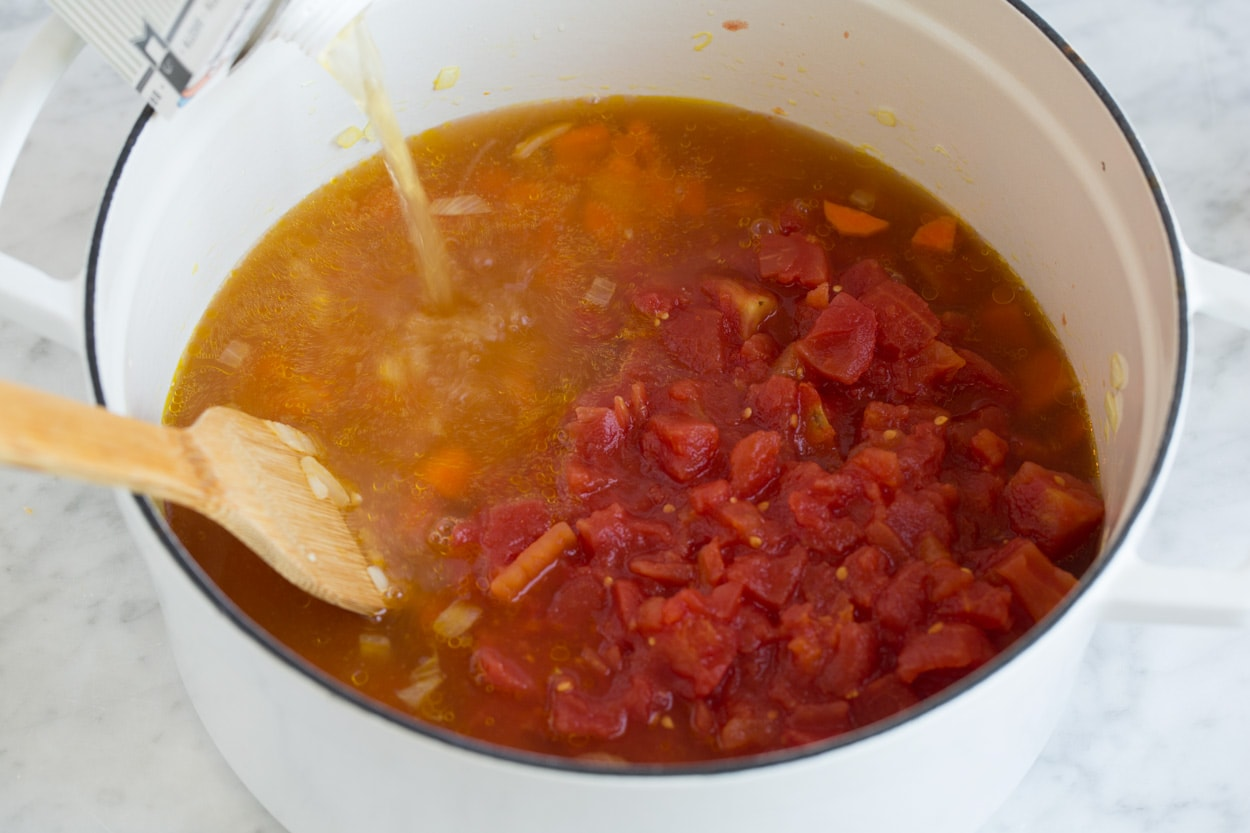 pouring broth and diced tomatoes into a large pot of lentil soup
