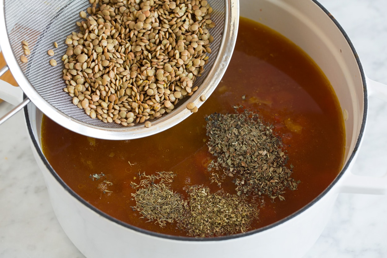 adding lentils and herbs into a pot of soup