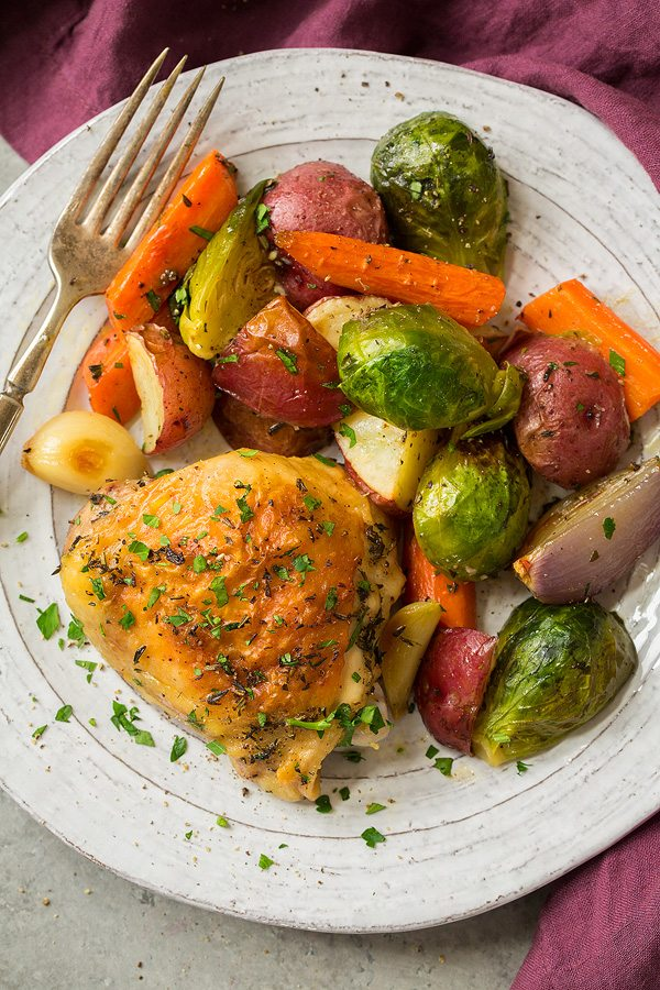 Roasted chicken thigh and roasted vegetables on a white serving plate.