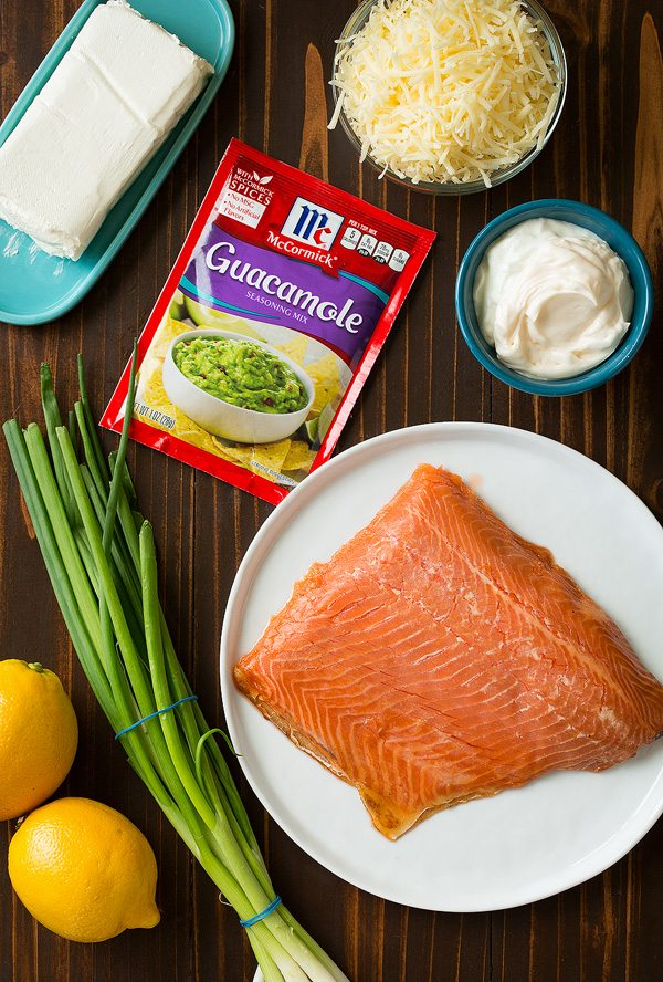 Ingredients needed for smoked salmon dip shown here. Includes cream cheese, mayonnaise, greek yogurt, white cheddar, green onions, lemons, seasoning, smoked salmon.