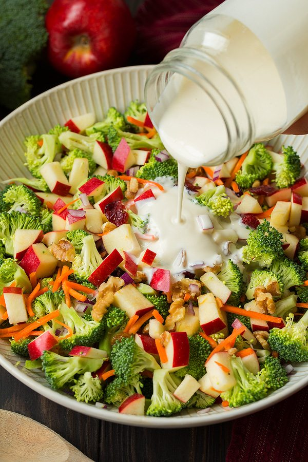 Broccoli Apple Salad with a creamy dressing getting poured over the top