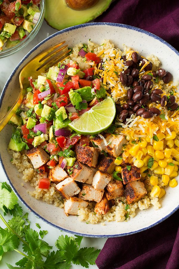 chicken Burrito bowls layered with quinoa, grilled chicken, black beans, corn, cheese and avocado salsa. Shown here in a white speckled bowl sitting on a marble surface.