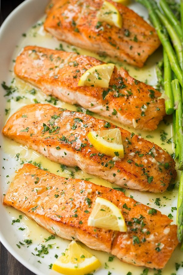 pan seared salmon fillets on a serving platter topped with a garlic lemon butter sauce. Served with a side of asparagus.