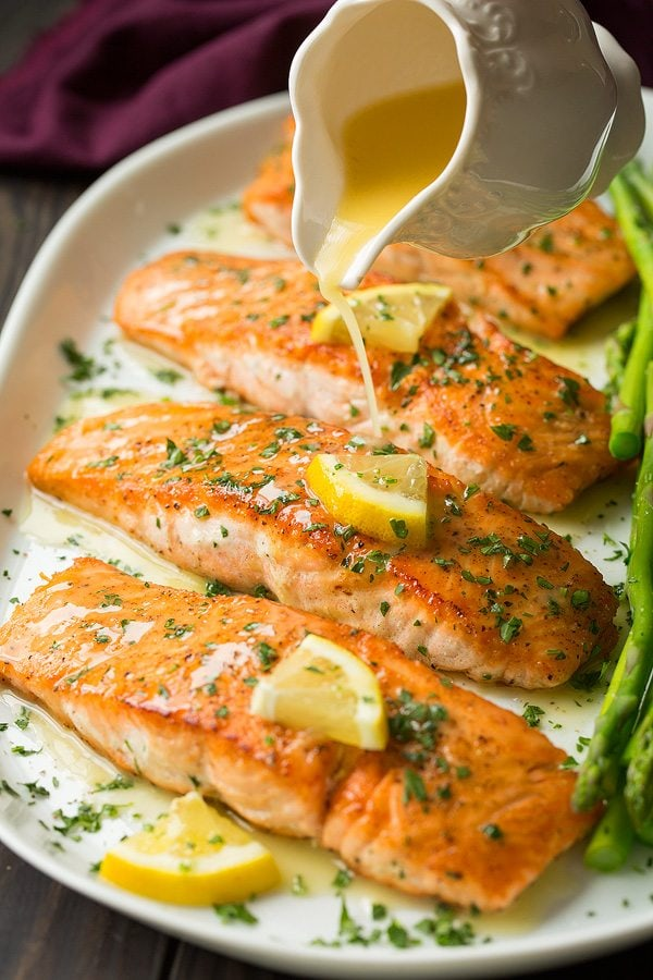 Pouring lemon butter sauce over pan fried salmon fillets on a white platter.