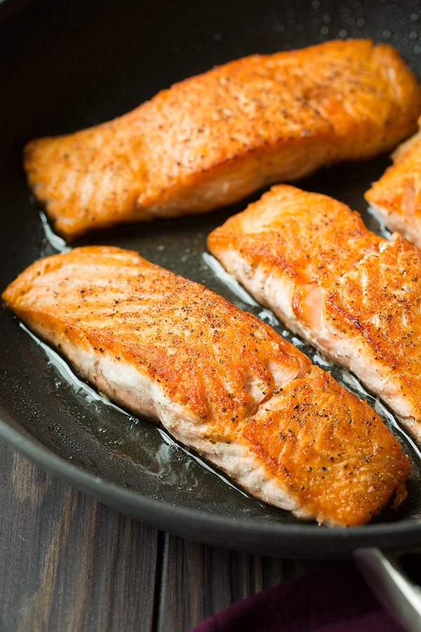 Showing how to sear salmon fillets in a skillet.
