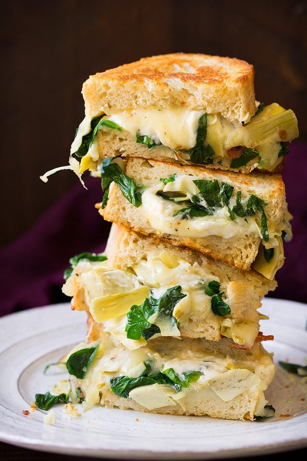 Stack of four grilled cheese sandwich halves on a white plate. Filling includes cheese, spinach and artichokes.