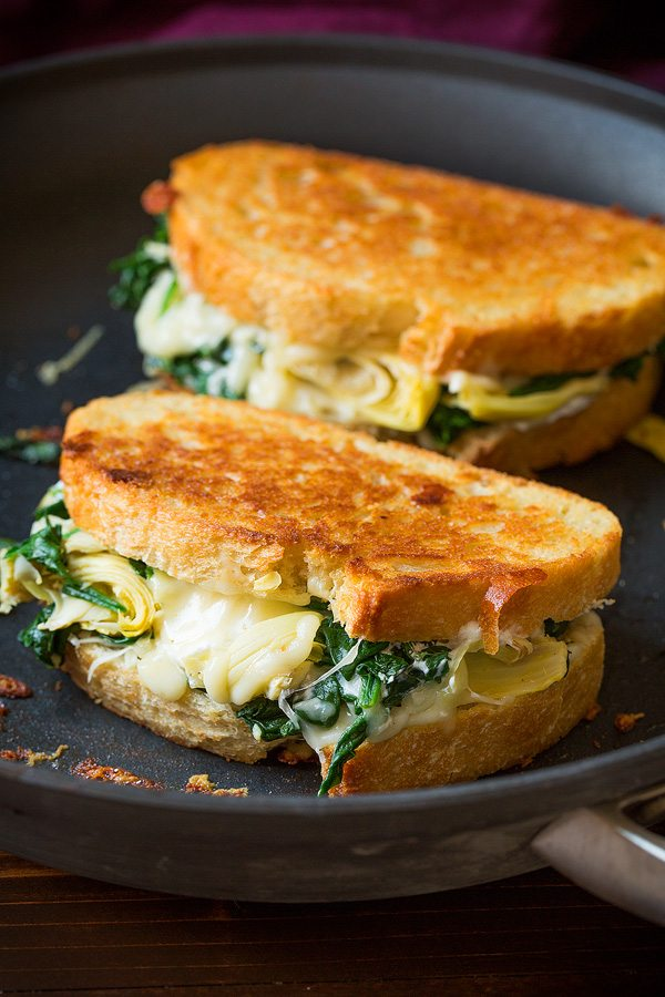 Two grilled cheese sandwiches in skillet.