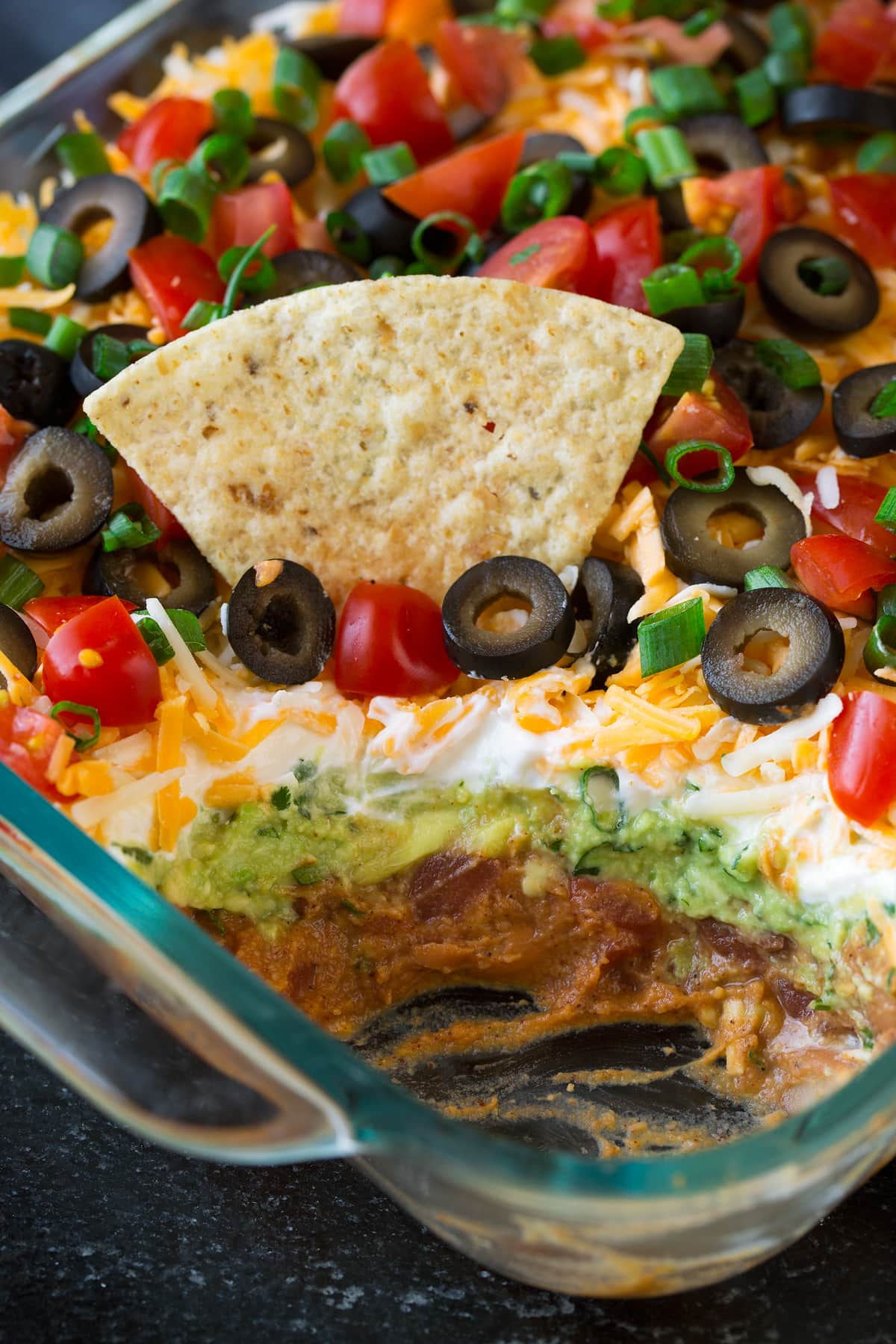 7 Layer Dip showing layer so of refried beans, guacamole, sour cream, cheese, olives, tomatoes and green onions.