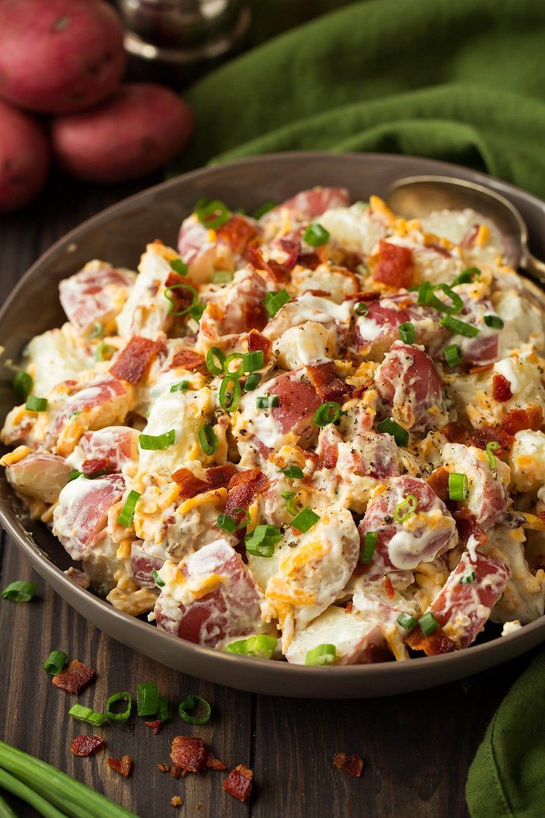 large bowl of cheddar bacon ranch potato salad with a spoon