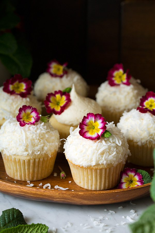 Coconut Cupcakes with coconut buttercream frosting garnished with edible flowers