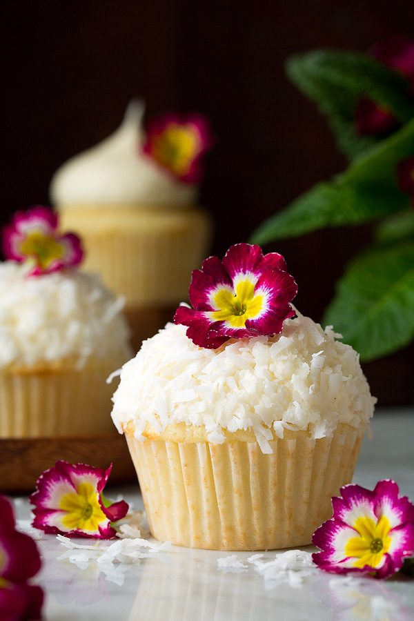 Coconut Cupcake with coconut buttercream frosting topped with shredded coconut and pink flower