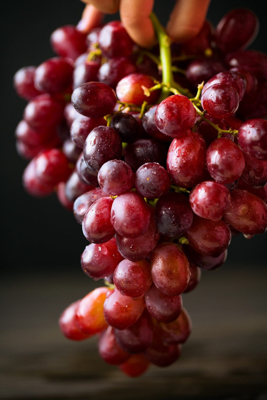 Close up image of red grapes dripping with water.