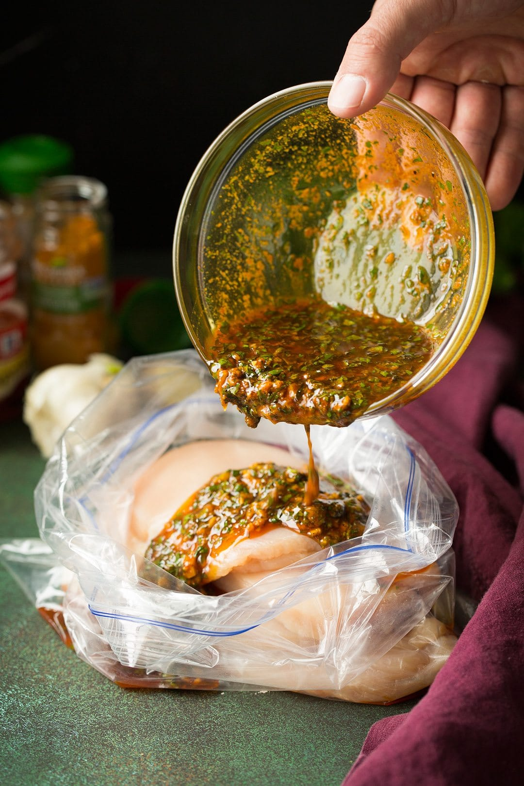 Pouring marinade over chicken breasts in a large resealable bag.