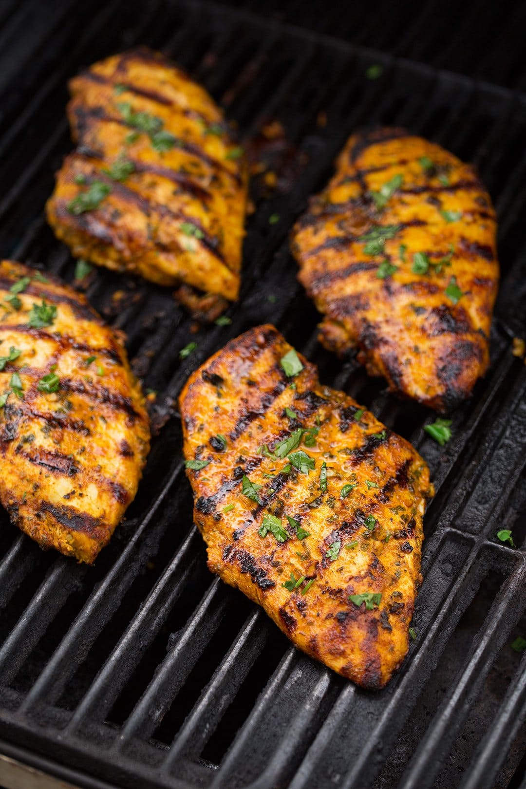 Four boneless skinless chicken breasts cooking on grill.