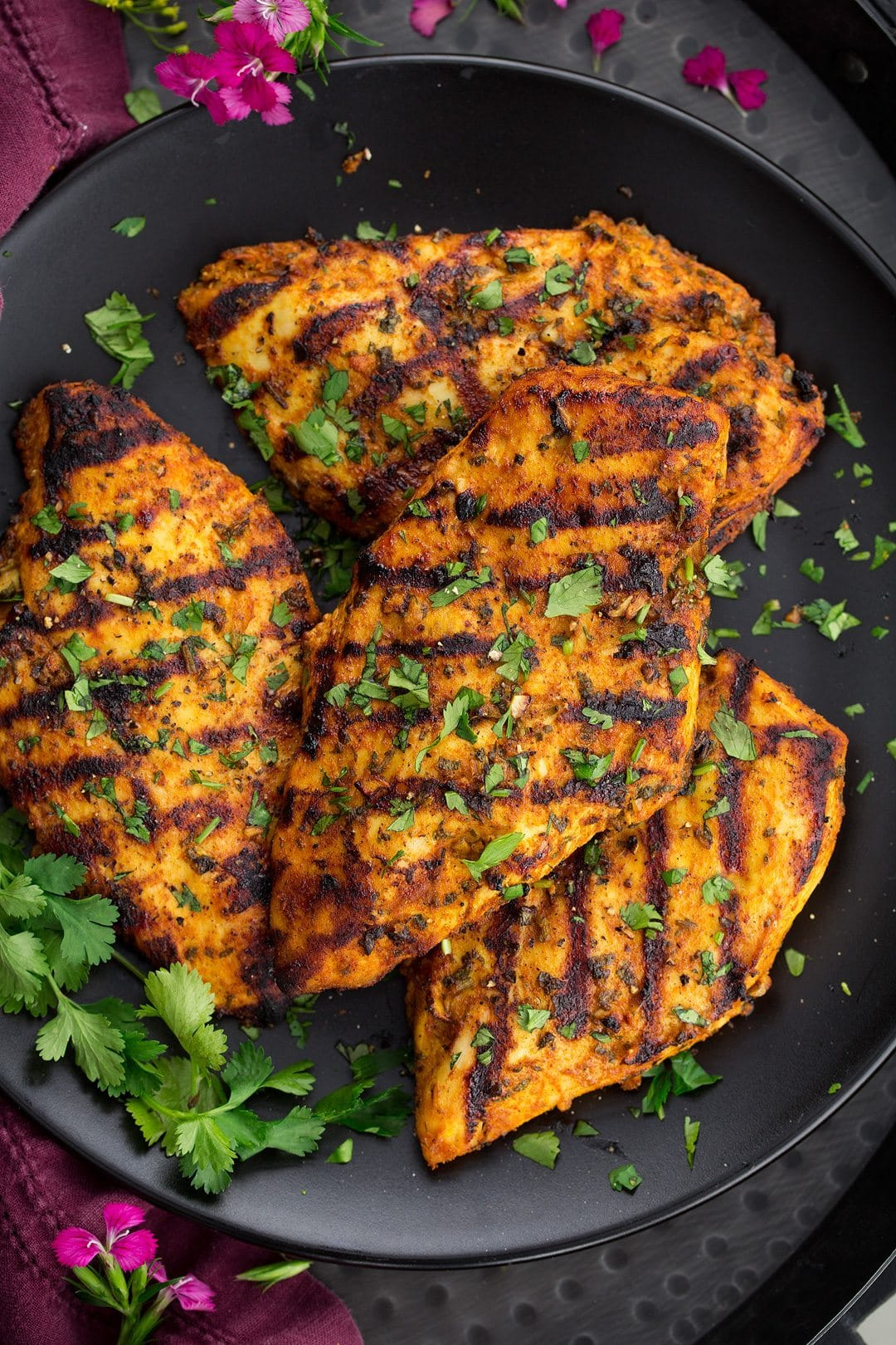 Grilled Moroccan Chicken on a dark plate with fresh parsley