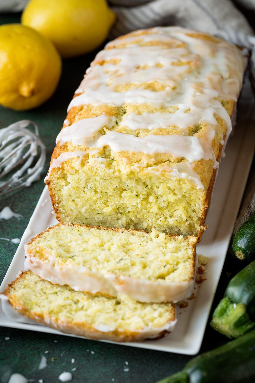 Lemon Zucchini Bread on a rectangular white serving dish. Two slices are cut from the loaf and laying in front to show inside of loaf.