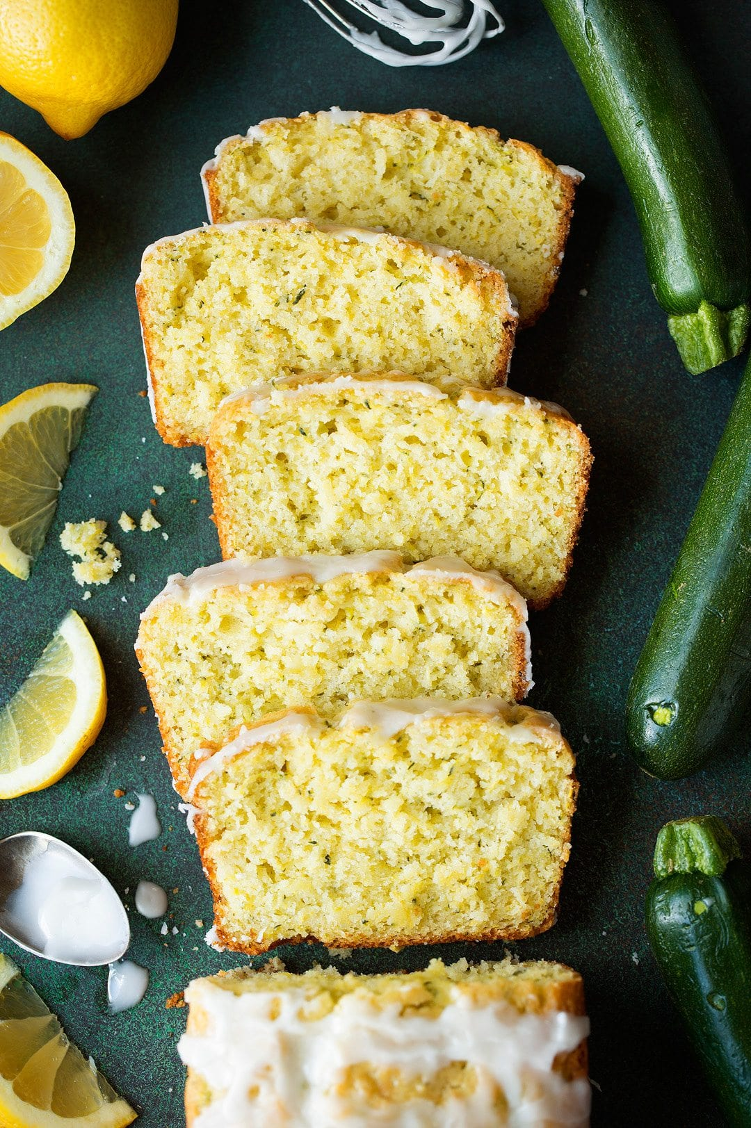 Overhead image of 5 slices of yellow Lemon Zucchini Bread laying on green surface with fresh zucchini and lemons surrounding the bread slices.