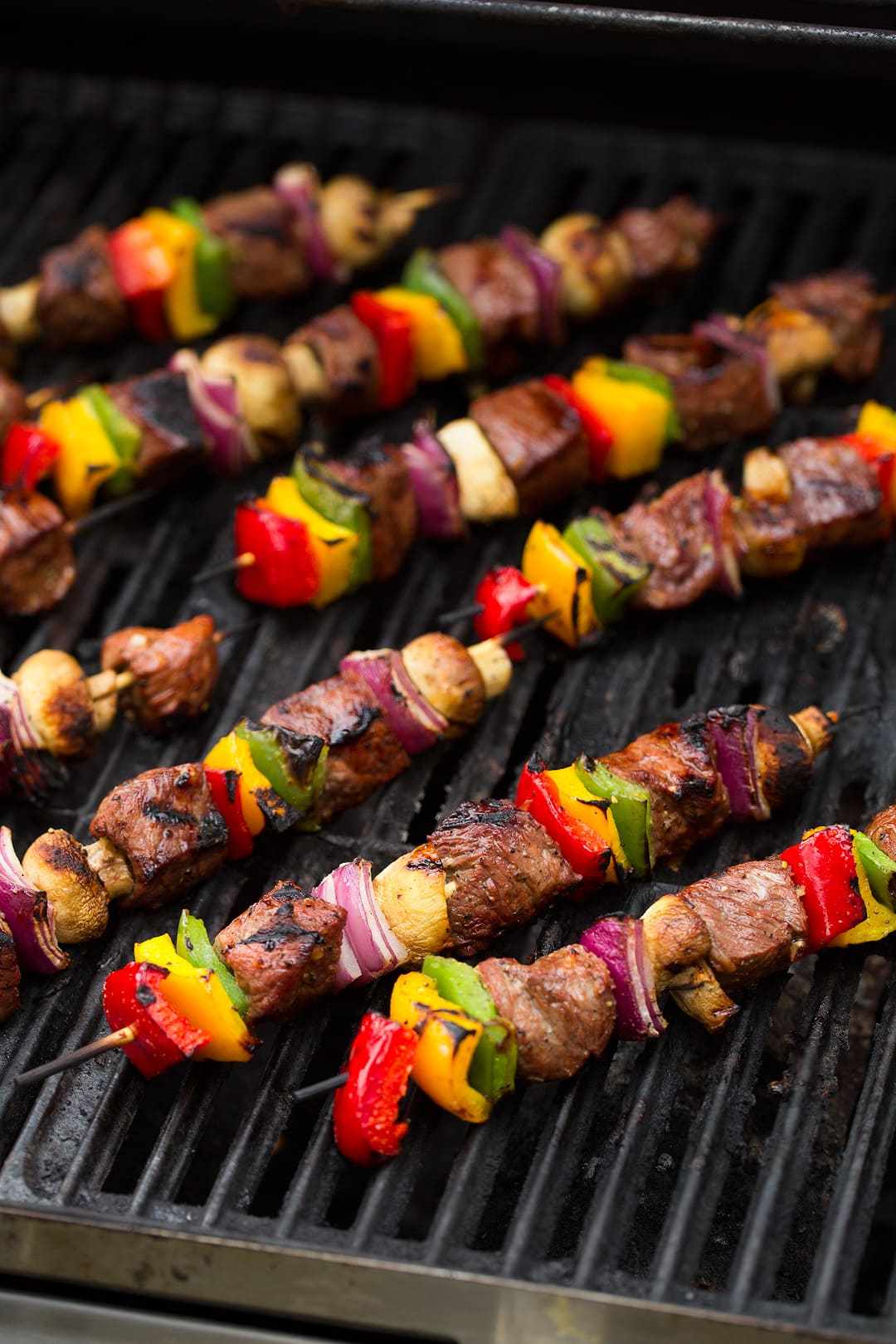 Nine steak kebabs shown here on a grill. Includes steak cubes and colorful fresh veggies on skewers.