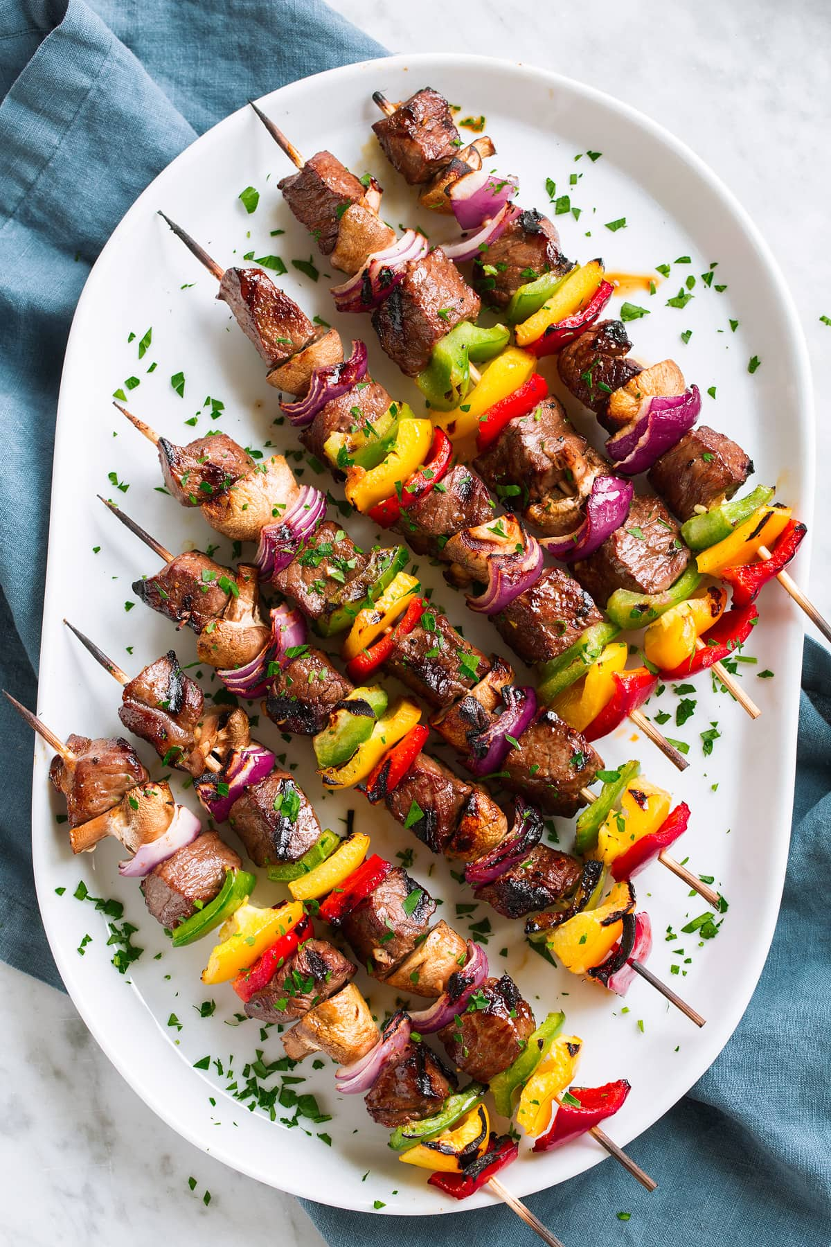 Seven steak kebabs on wooden skewers on a white platter set over a blue cloth on a marble table.