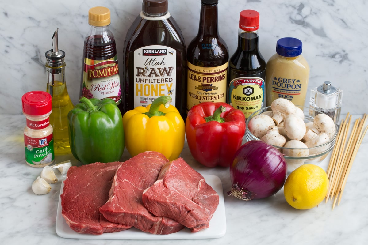 Ingredients needed to make steak kebabs shown here including steaks, bell peppers, red onion, garlic, lemon, dijon mustard, soy sauce, Worcestershire, honey, red wine vinegar, olive oil, garlic powder.