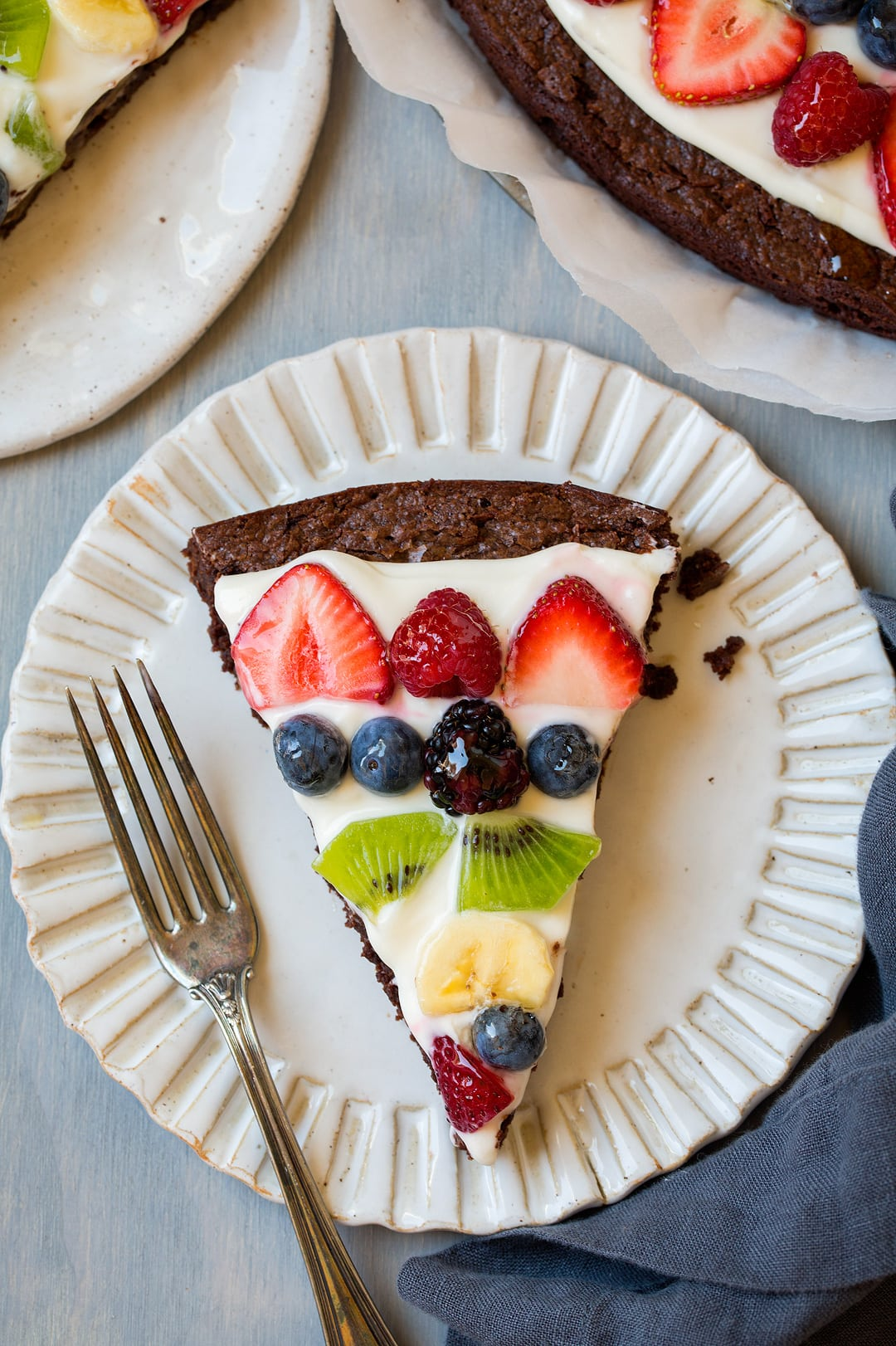 Brownie fruit pizza slice on a white plate, sitting on a blue wooden surface.