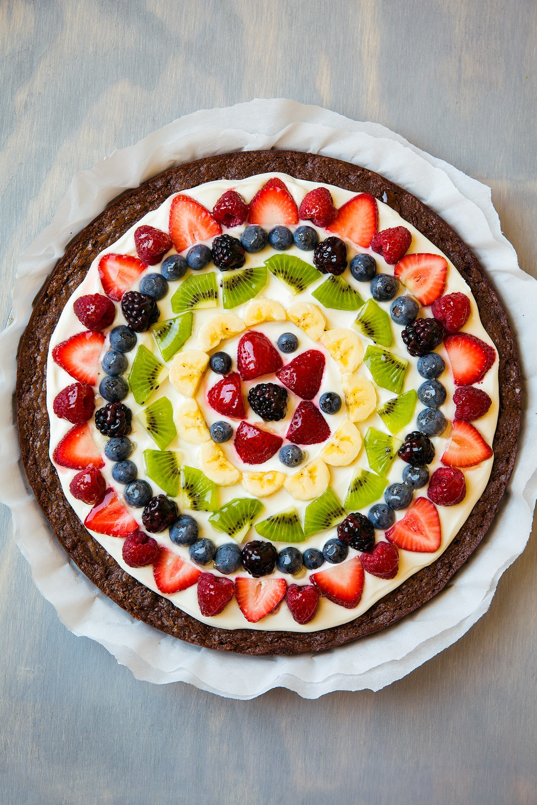 Brownie Fruit Pizza topped with cream cheese frosting, strawberries, raspberries, blueberries, blackberries, kiwi, and bananas.