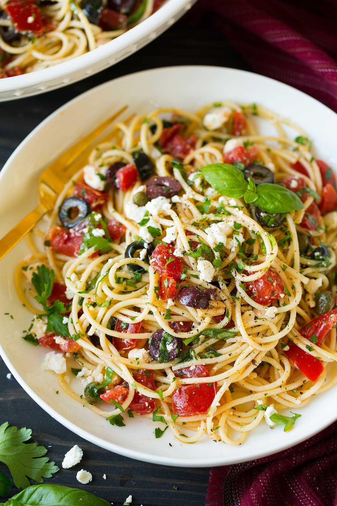 Greek spaghetti layered with tomatoes, black olives, kalamata olives, feta, basil, garlic, olive oil. Served in a pasta bowl on a brown wooden surface.