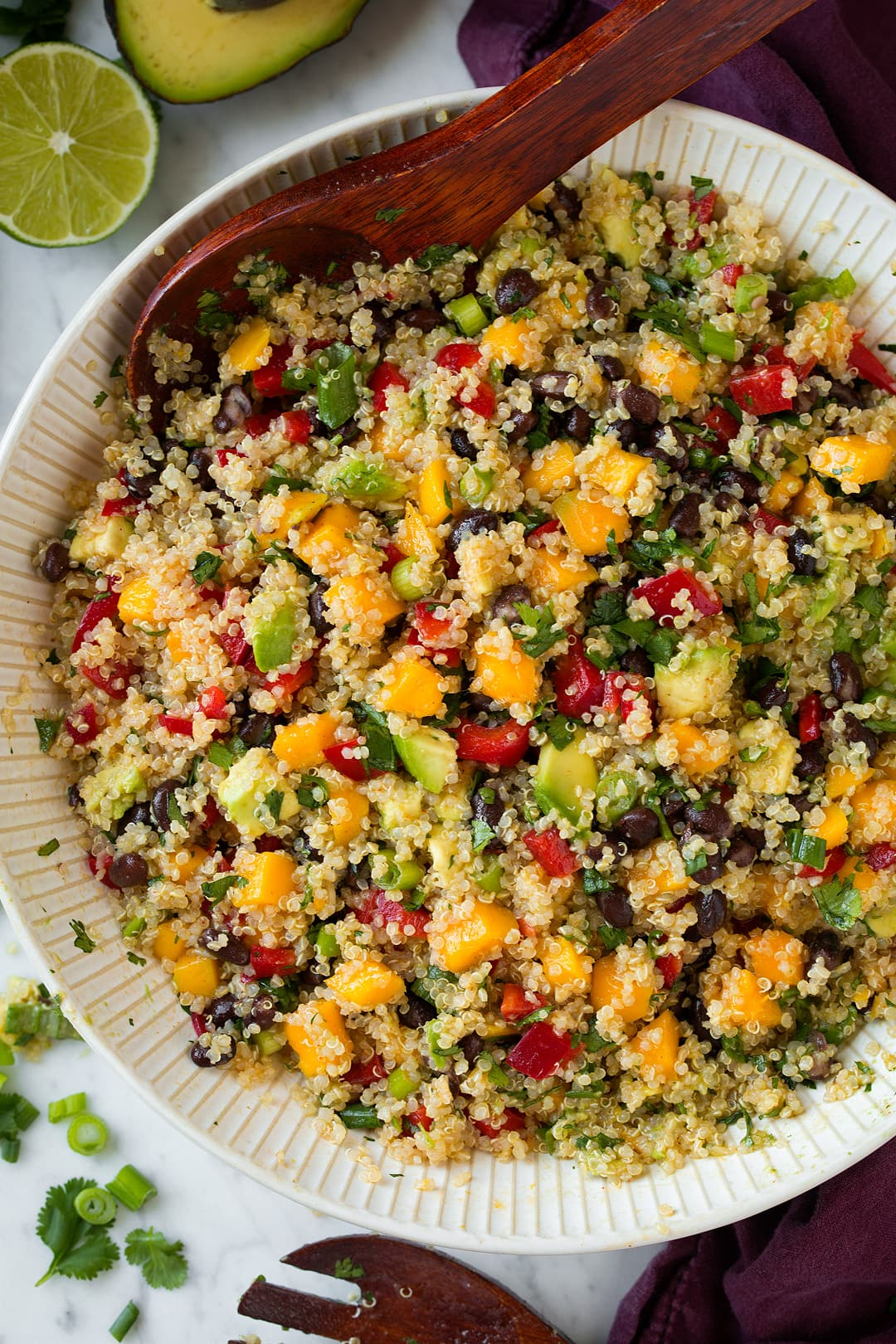 Overhead image of Quinoa Salad in a large white ceramic bowl, with wooden spoon for serving.