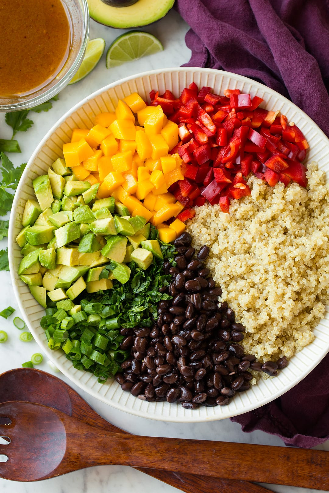 Quinoa black bean salad ingredients shown in individual portions before tossing in a white salad bowl.