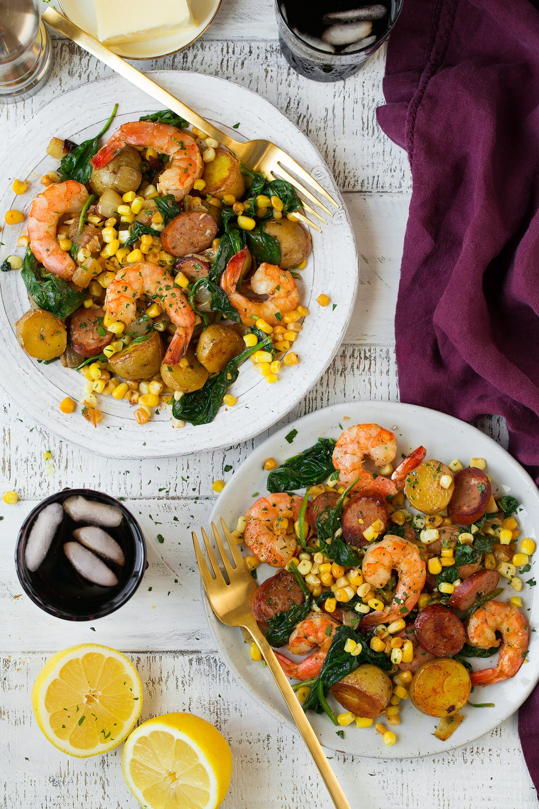 Shrimp boil shown here on two white serving plates set over a white wooden background with a maroon napkin and fresh lemons on the side.