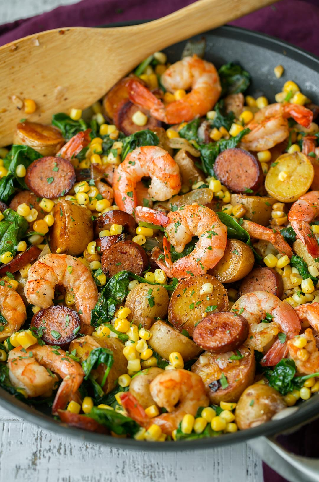 Shrimp Boil that includes shrimp, potatoes, corn, sausage, old bay seasoning, spinach and lemon