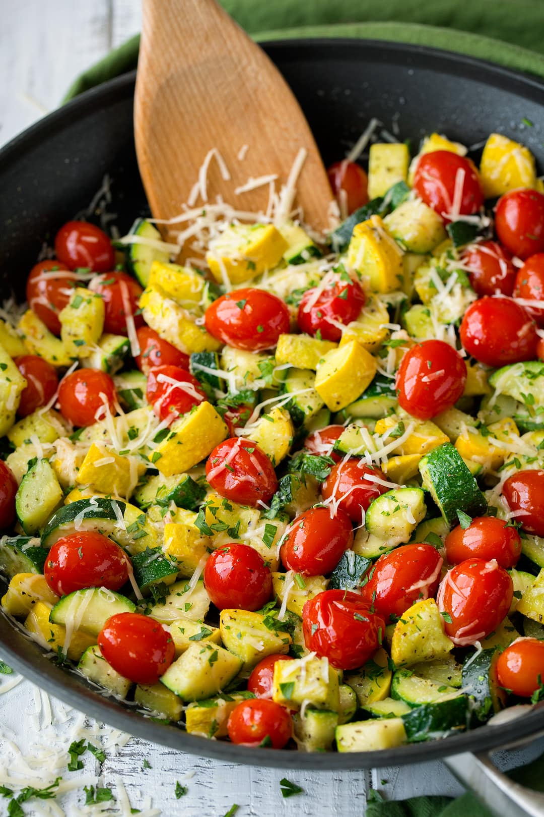 sauteed zucchini and squash with tomatoes in a large black skillet.