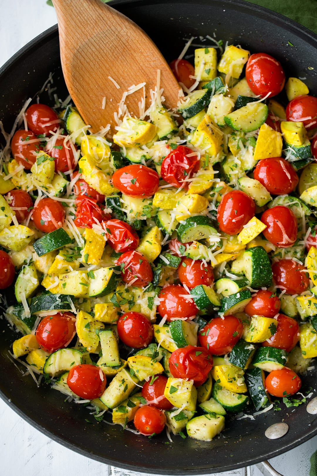 Overhead image of sauteed zucchini, squash and tomatoes in a large dark skillet.