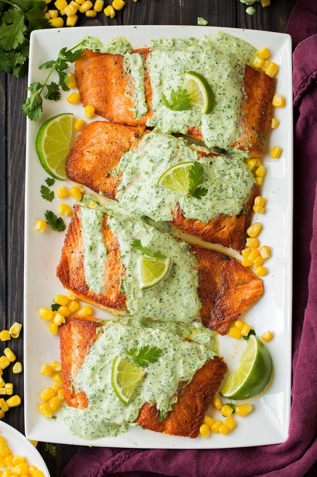 four cilantro lime salmon fillets on white platter