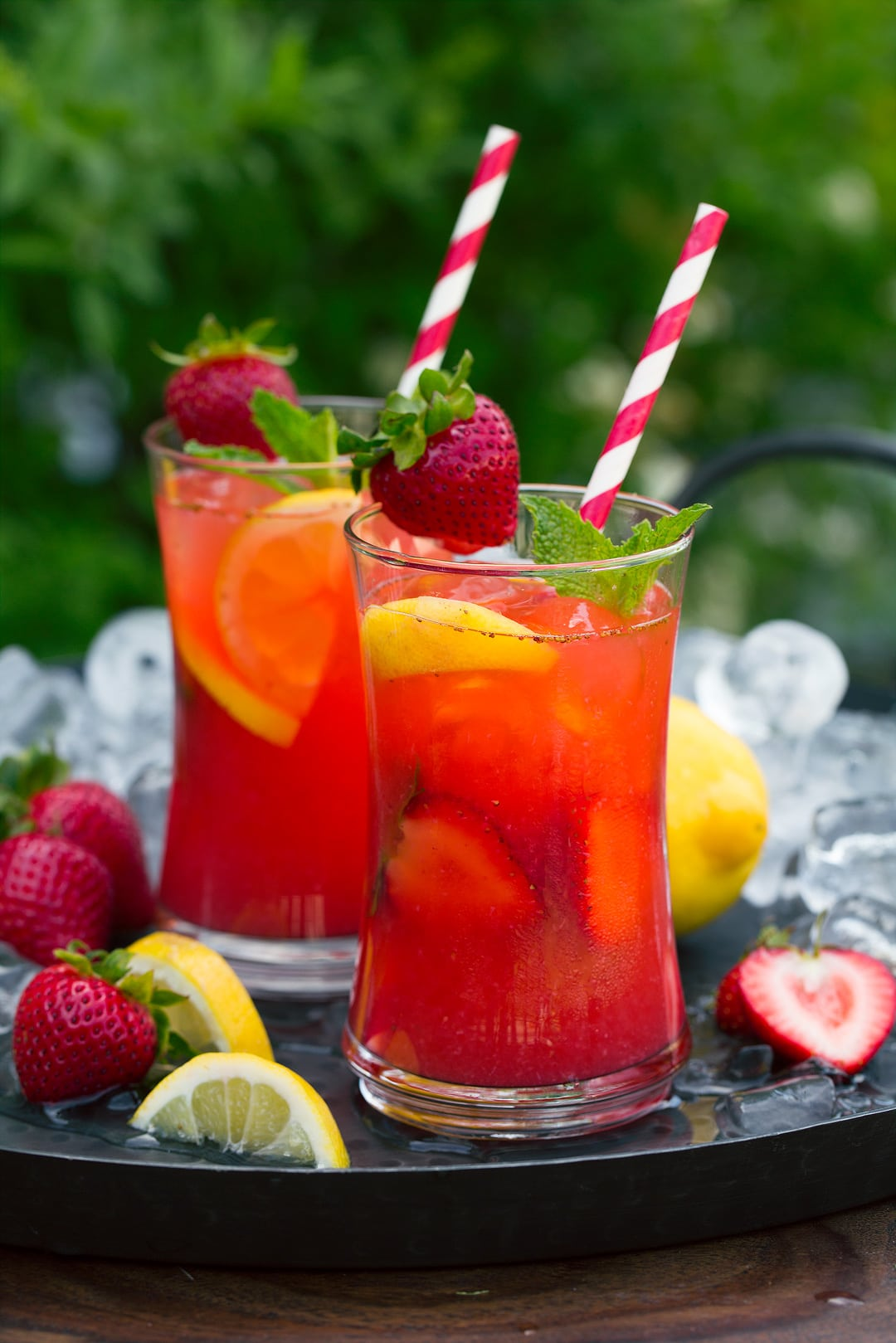 two glasses of Strawberry Lemonade on tray with lemon wedges and fresh strawberries