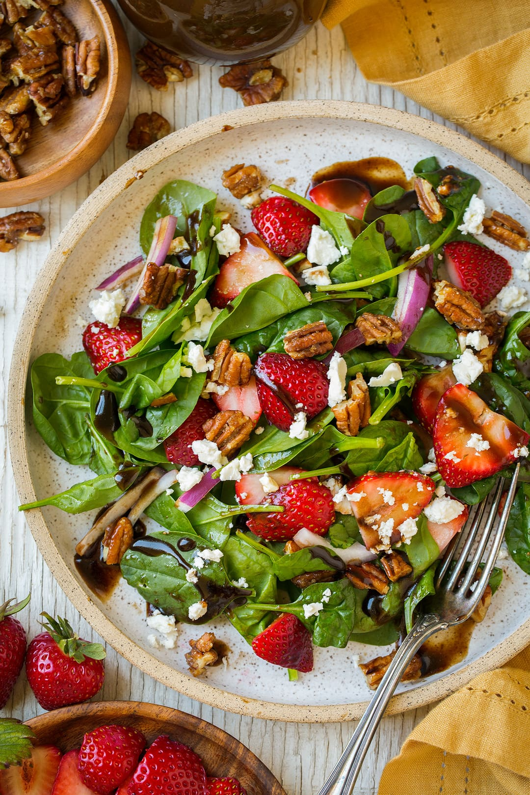 An overhead shot of a Strawberry Spinach Salad on a plate with chopped pecans