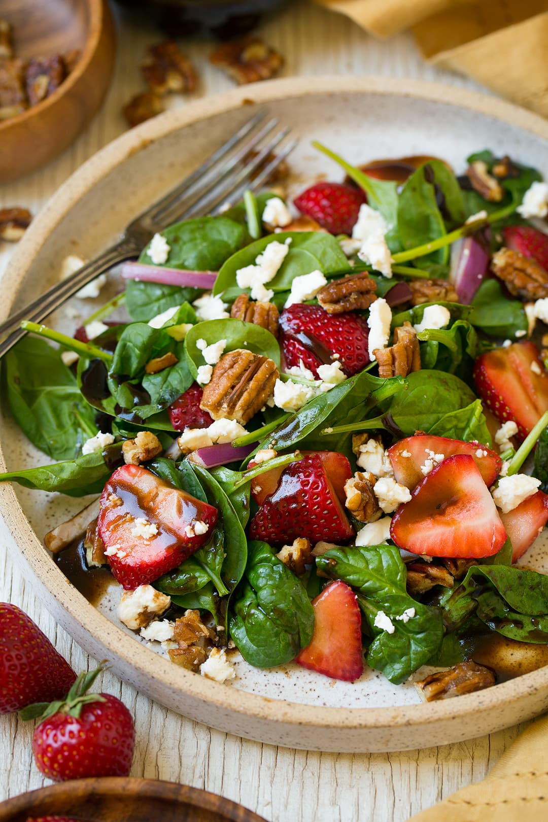 A Strawberry Spinach Salad in a bowl with a fork