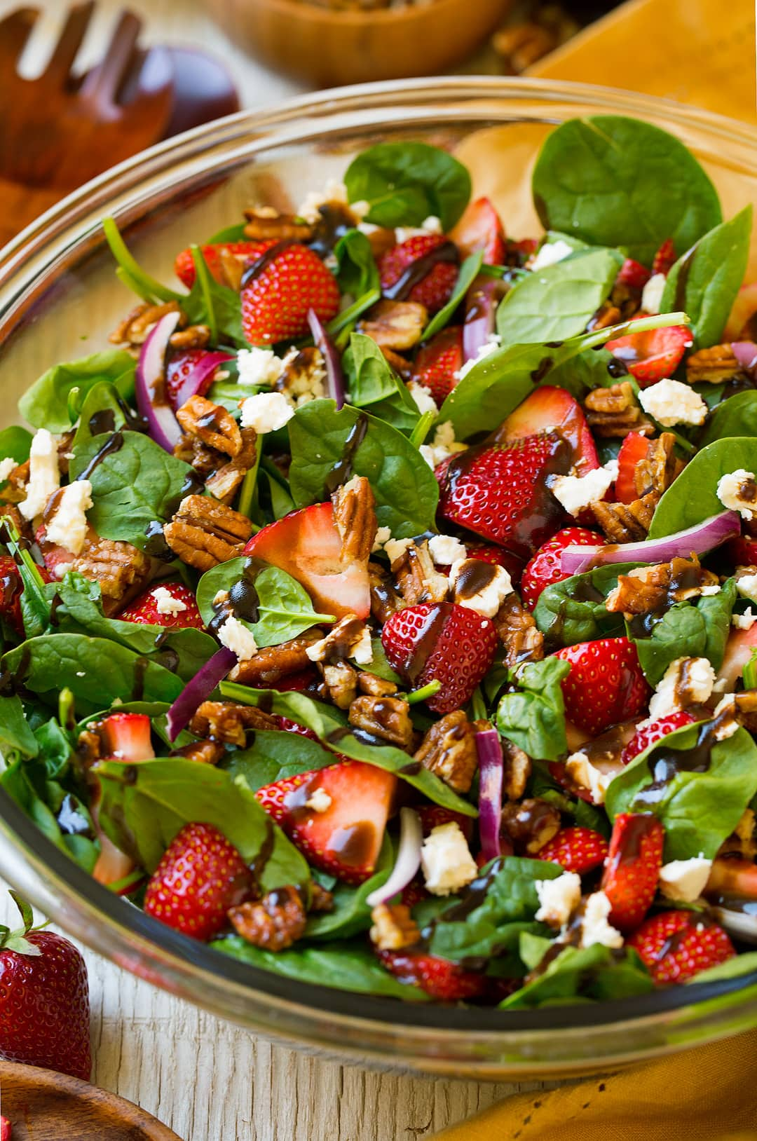A close up of a Strawberry Spinach Salad in a glass bowl topped with a balsamic vinaigrette