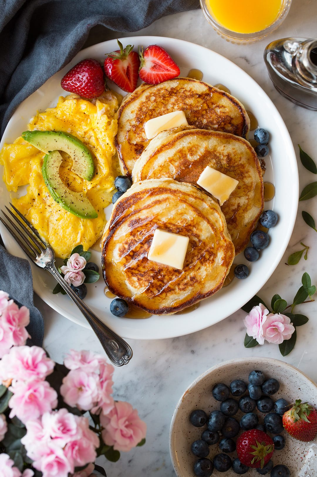 Three buttermilk pancakes on a large white plate dotted with slabs of butter and drizzled with maple syrup. Included on the side are scrambled eggs and fresh fruit.