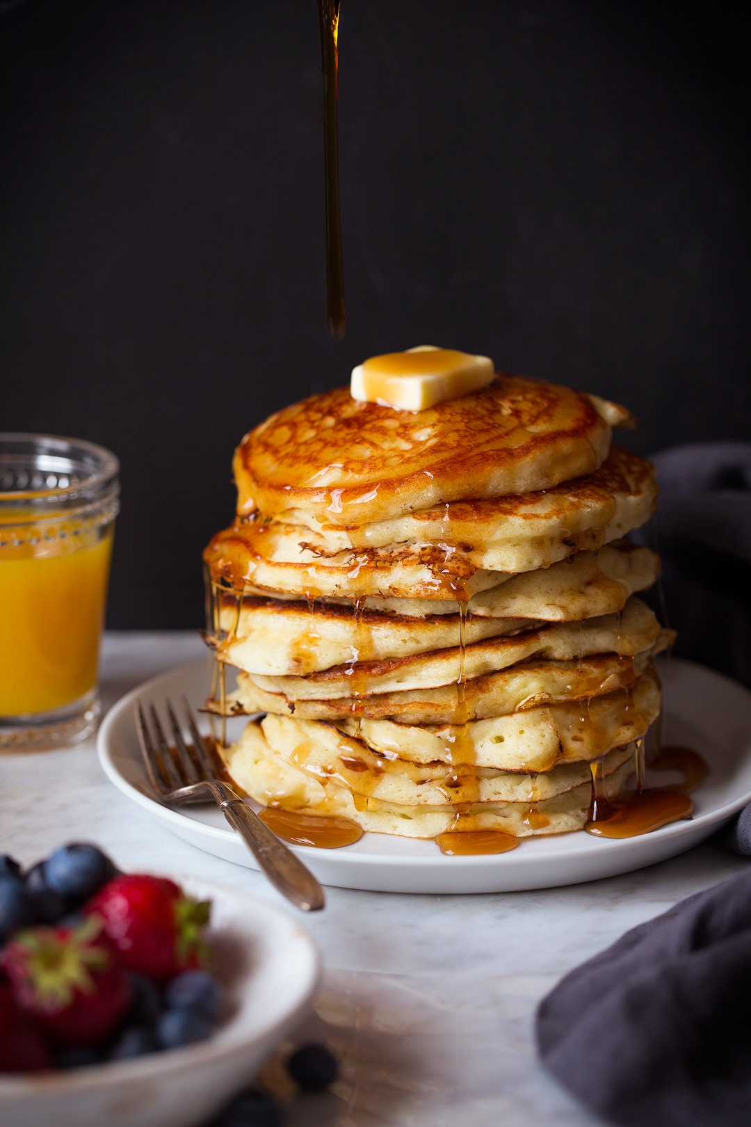 Stack of pancakes on a plate. Syrup is being poured over the top.