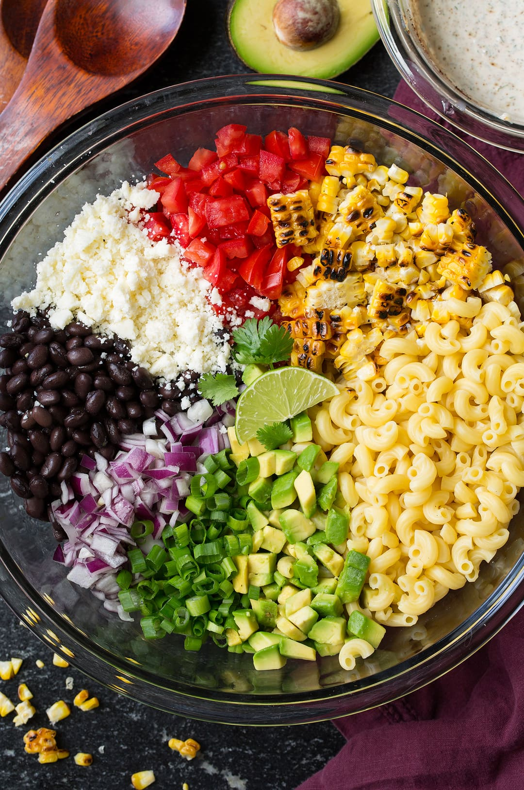 Mexican macaroni salad ingredients in a large glass bowl before tossing. Ingredients include macaroni, charred corn, black beans, avocado, tomato, green onion, red onion, and cotija.