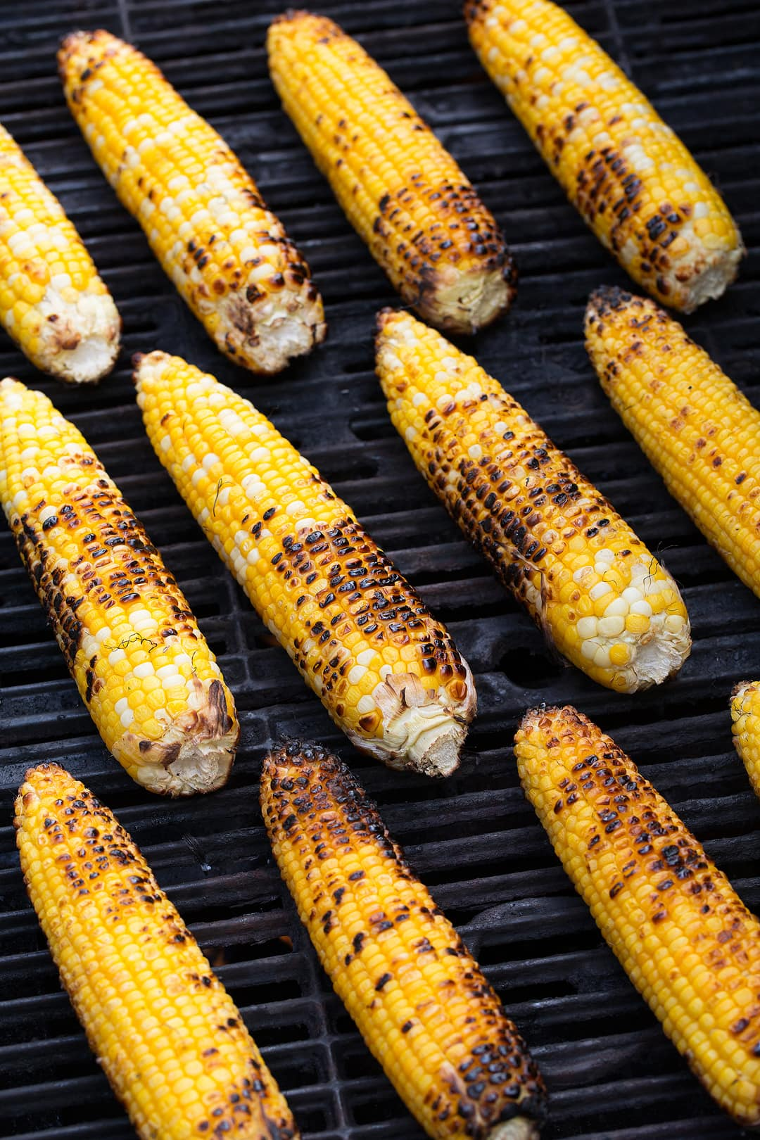 12 cobs of fresh corn on a grill to make Mexican Street Corn.