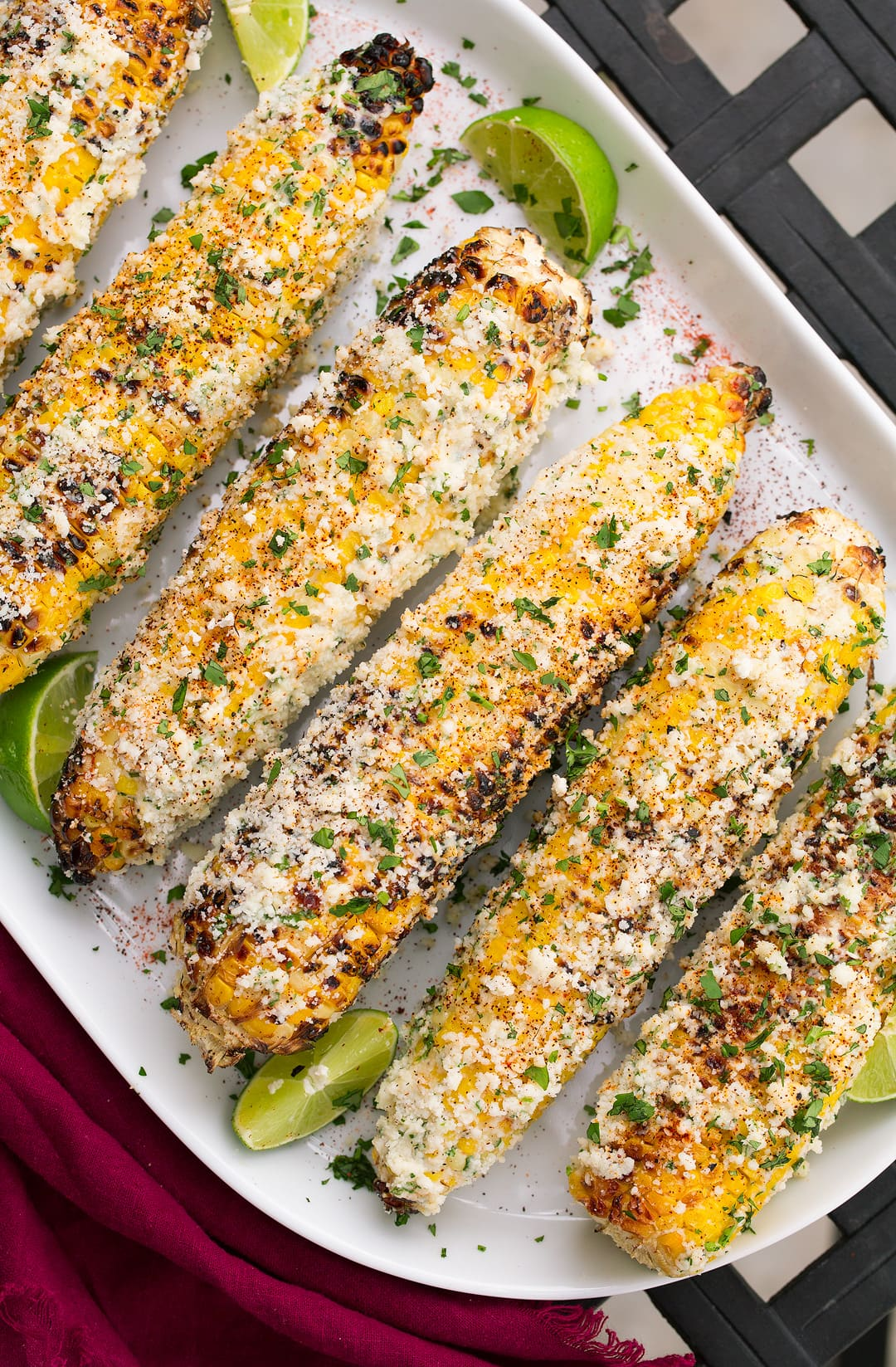 Mexican Street Corn on a large white platter. Corn cobs are topped with mayonnaise, cotija cheese, and chili powder.