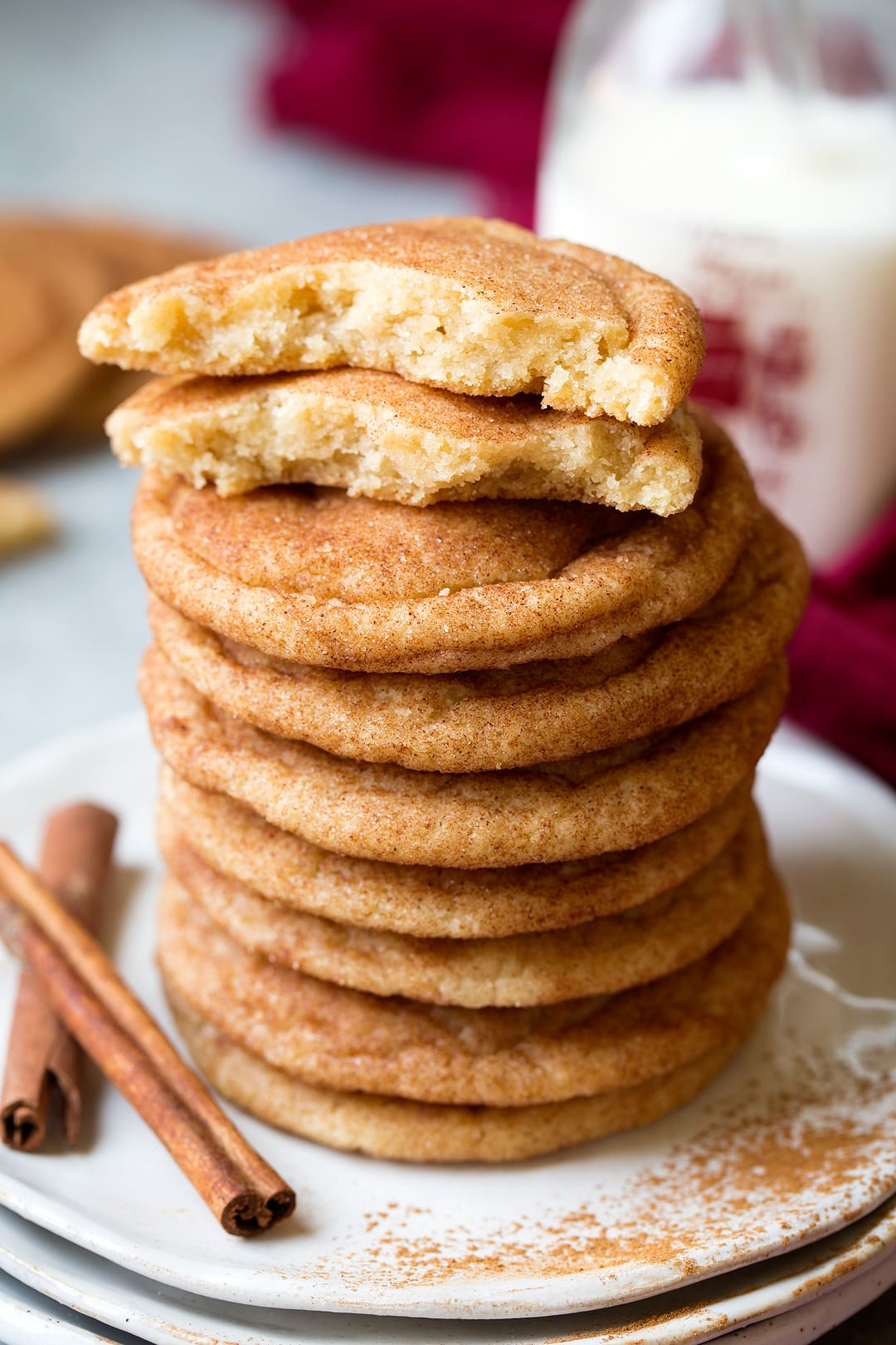 Stack of snickerdoodle cookies on a plate with one cooke on top broken in half to show texture of interior.