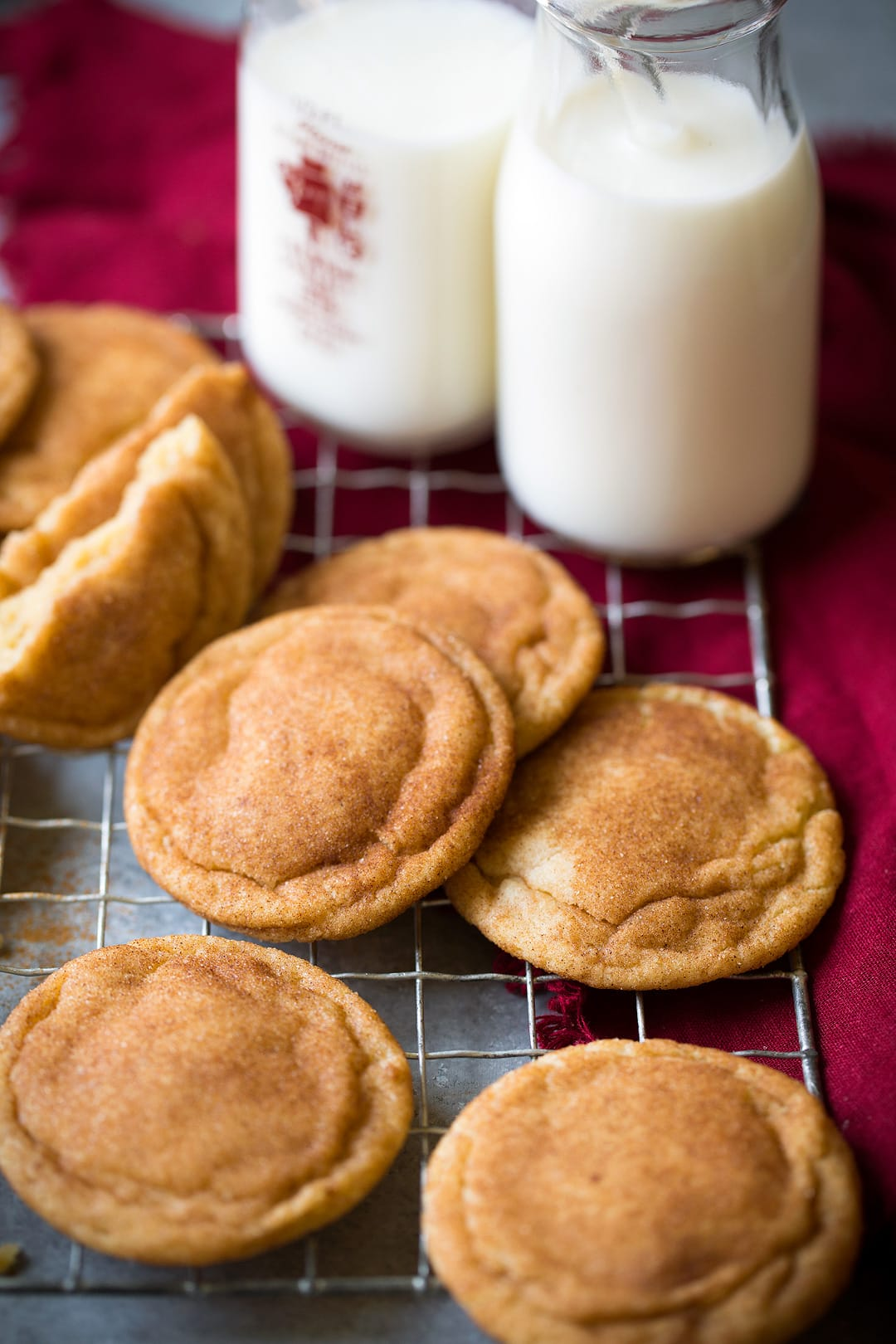 Row of snickerdoodle cookies on a wire cooling rack set over a grey surface with a red napkin on the side and two glass of milk in the background.