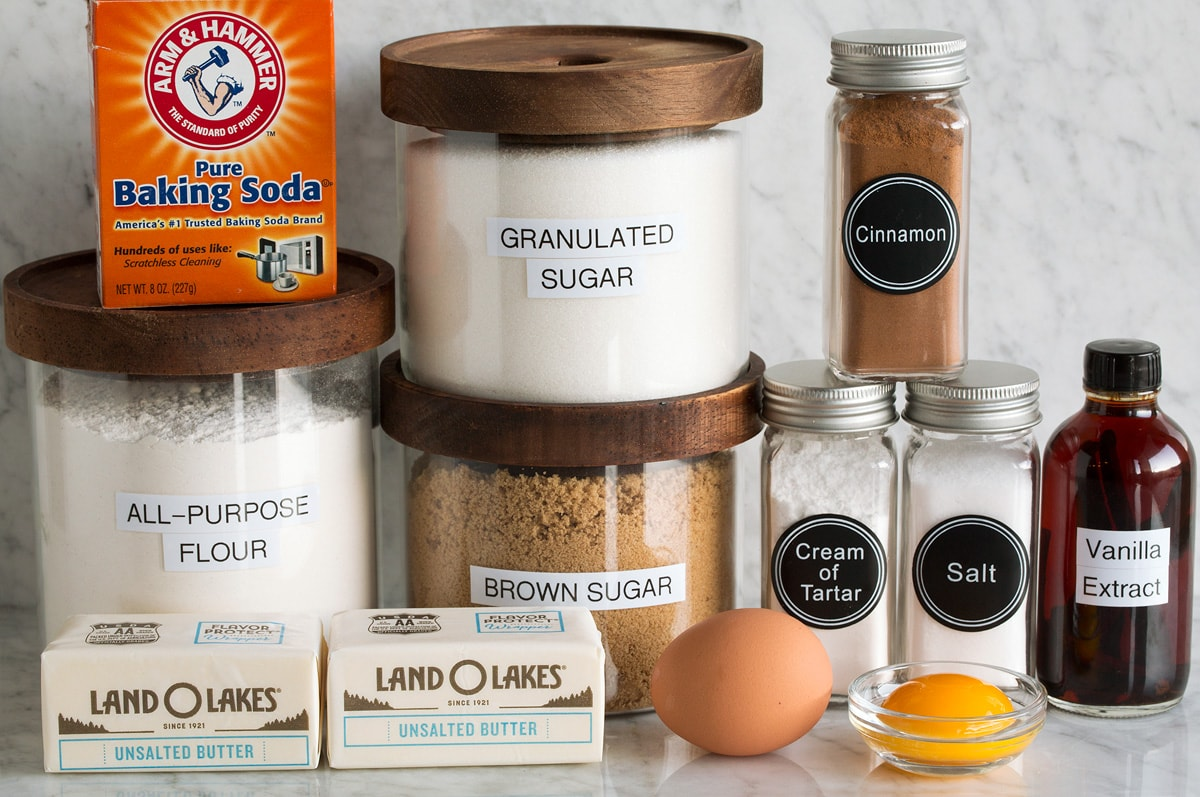Image of ingredients used to make Snickerdoodle cookies. Includes flour, granulated sugar, brown sugar, egg, egg yolk, butter, salt, cream of tartar, cinnamon, vanilla and baking soda.