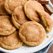 Image of snickerdoodles cookies shown from the side layered together on a white plate with cinnamon sticks in the background. Plate is resting on a striped blue cloth and wooden platter.